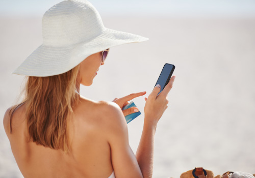 female on beach in beach hat using smartphone and credit card to shop online