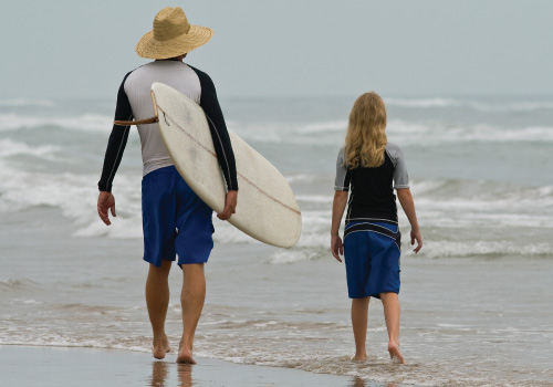 adult with hat and surfboard and child on beach walking towards the water