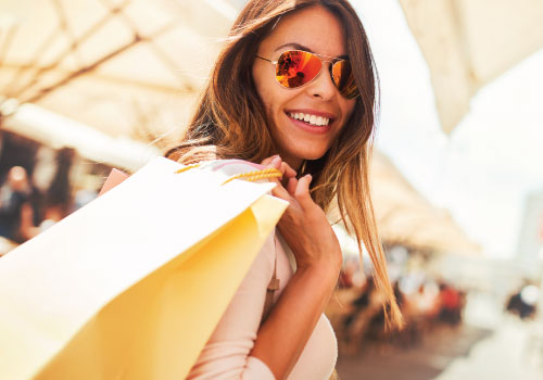 Young female adult with sunglasses and a handful of shopping bags carried over her shoulder, smiling