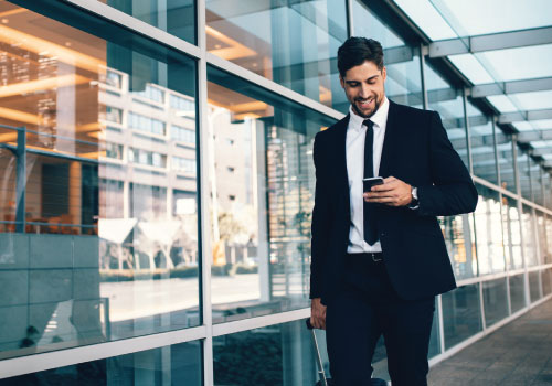 Young adult male professional walking along a modern glass building looking at his smartphone and smiling