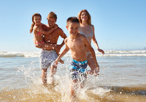 family splashing in water on beach all smiling